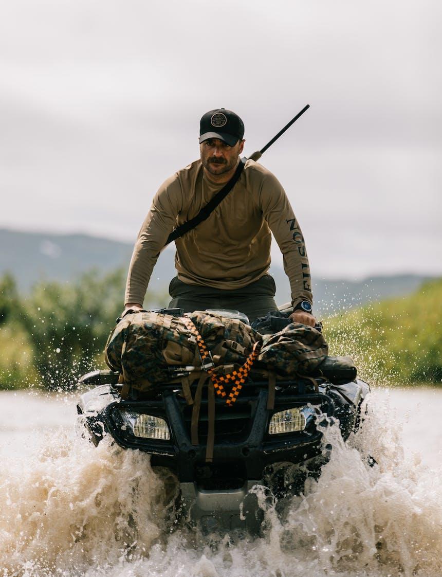 brett riding a 4 wheeler through a creek