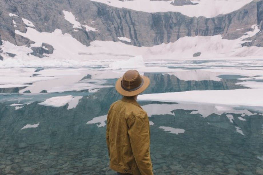 man in brown stetson and coat looks out at glacial pond with ice floats and sheer rock faces with snow