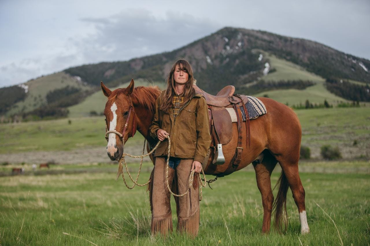 Hilary standing with her horse with mountains in the background