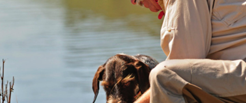 man communes with dog at bank of lake