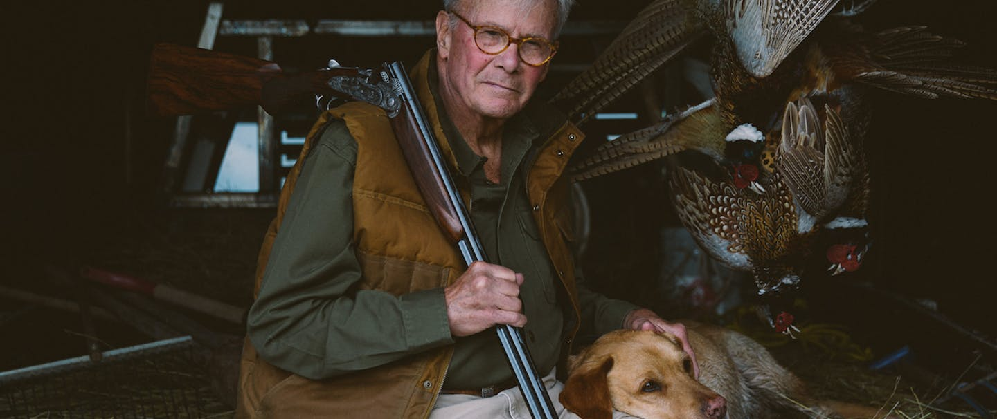 Tom Brokaw sits next to taxidermy pheasant and his hunting dog with a shotgun over his shoulder