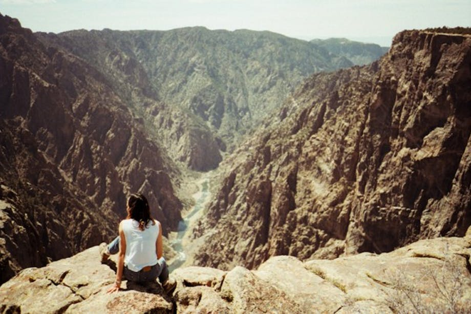 woman sits looking at sheer rock faces of black canyon
