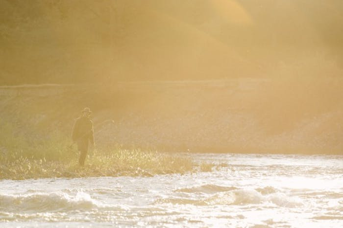 sunburst silhouette of man approaching river holding flyfishing rod