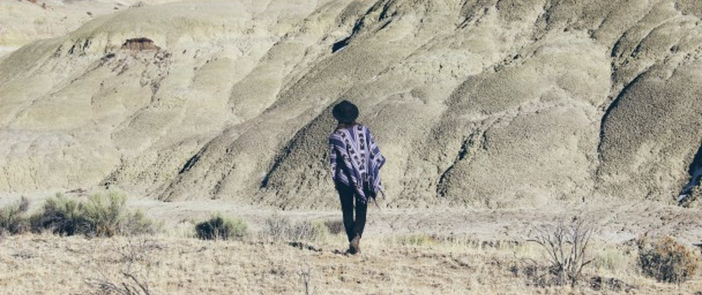 person in purple shawl and black hat walking toward stark white hills