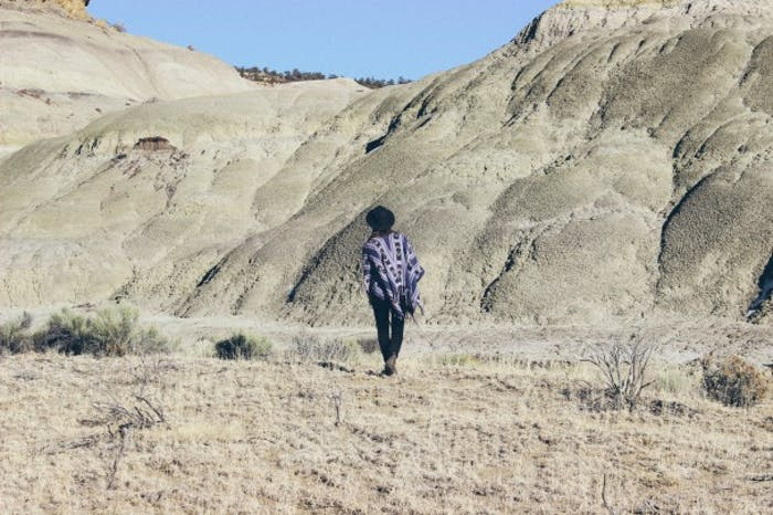person in purple shawl and black hat walking toward stark white hills