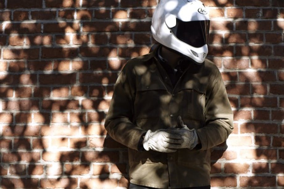 person in white motorcycle helmet with green filson jacket and white gloves in front of brick wall