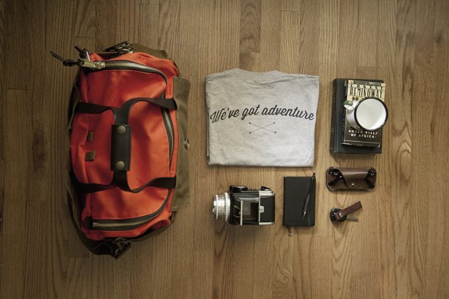 Packing setup on wooden floor duffel, shirt journal camera glasses and book