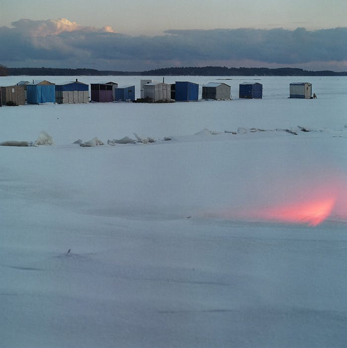 line of small structures in frozen tundra at sunset