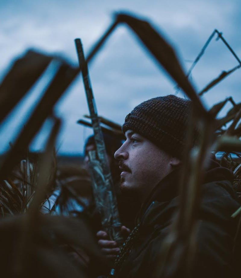 Filson Life - Winter Duck Hunting, hunters stand among reeds holding camouflage shotgun