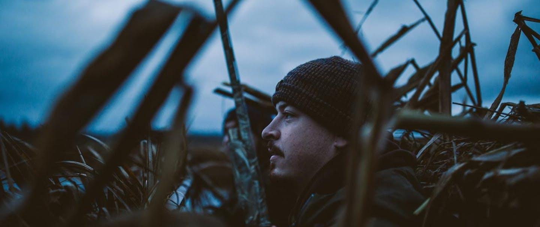 Two men in a duck blind before sunrise survey an open field.