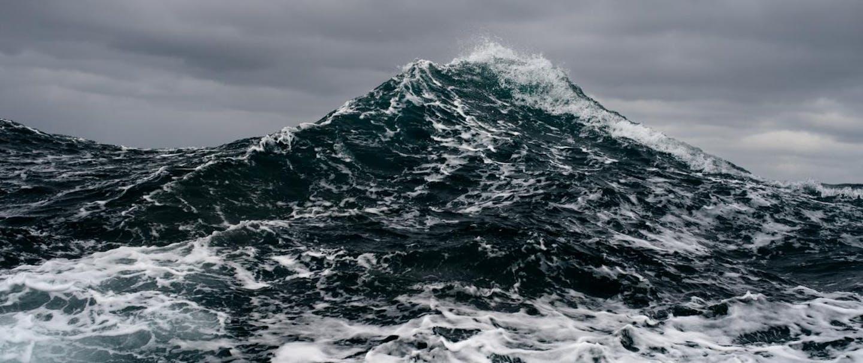 Filson Life - Photographer Corey Arnold. large sea wave rises toward the clouds like a mountain
