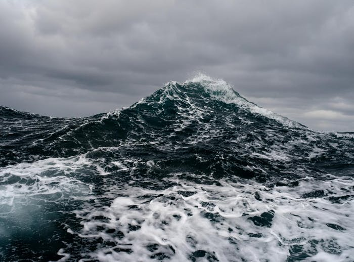 Filson Life - Photographer Corey Arnold. large sea wave rises toward the clouds like a mountain