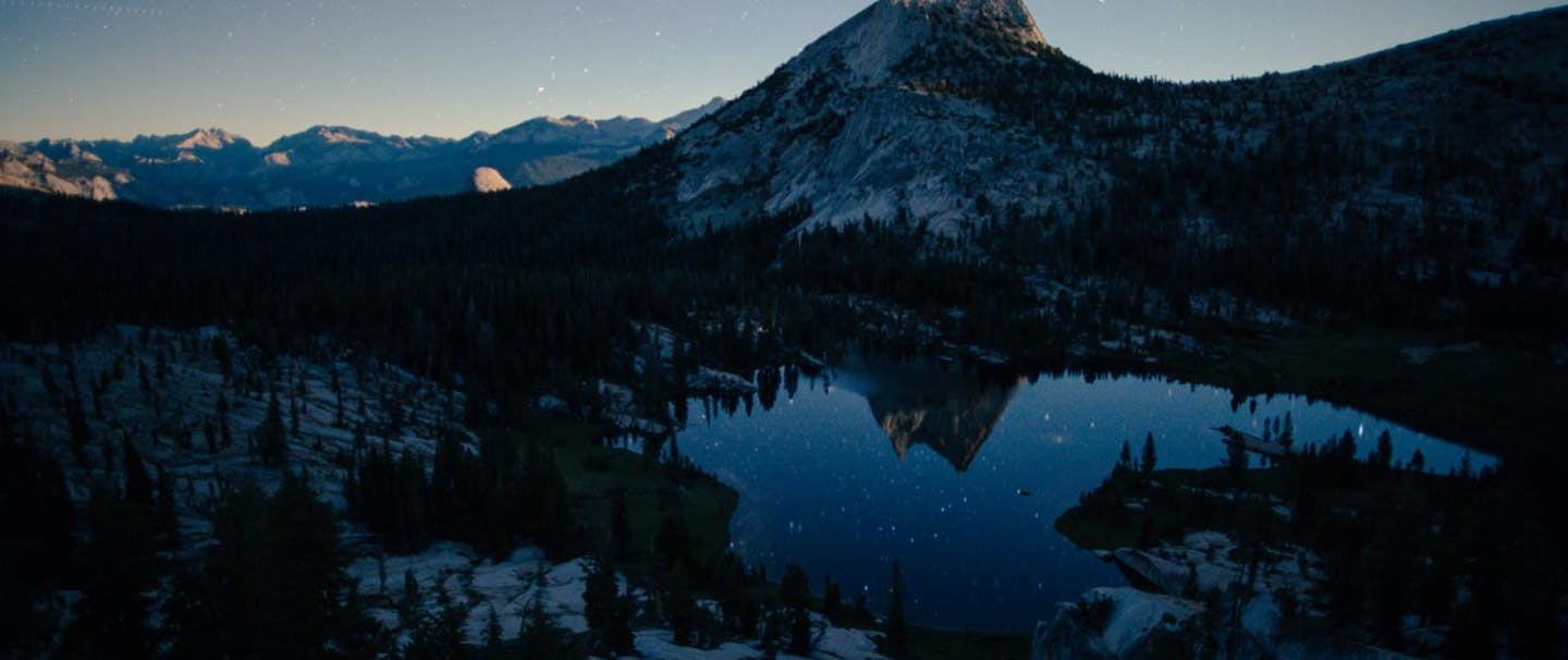 peak in yosemite california reflecting in mountain pond with stars visible