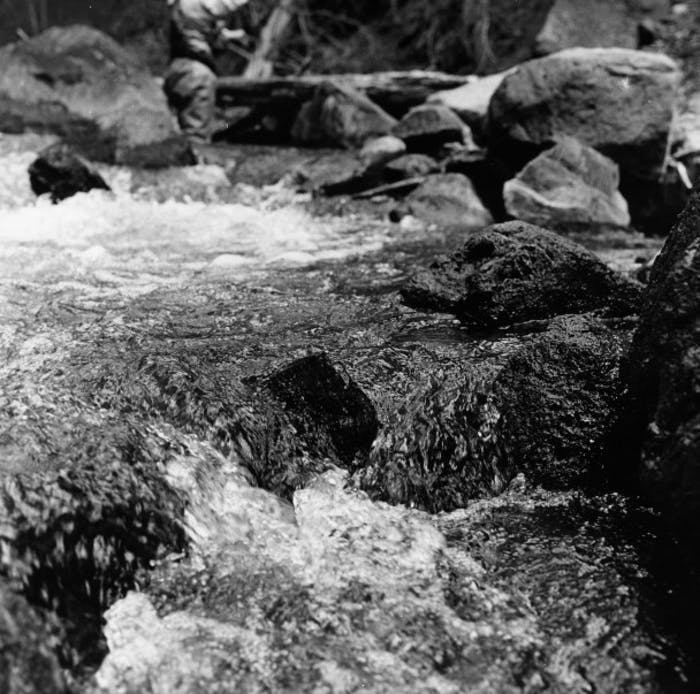 man stands upriver in rushing water among large rocks
