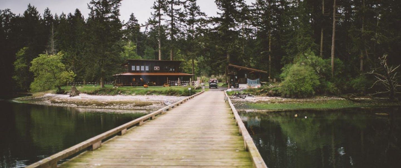 wooden bridge runs over water toward cabin in the woods