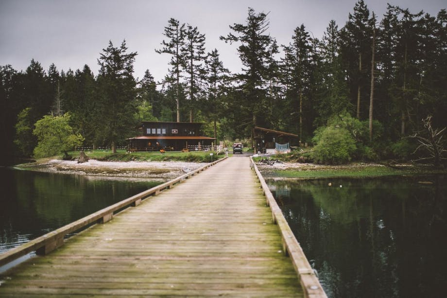 wooden bridge runs over water toward cabin in the woods