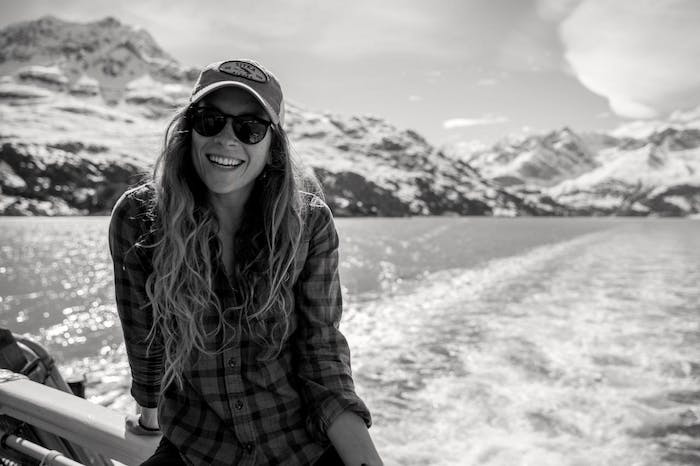 woman on boat in sunglasses and hat and plaid shirt with snowy mountains in background