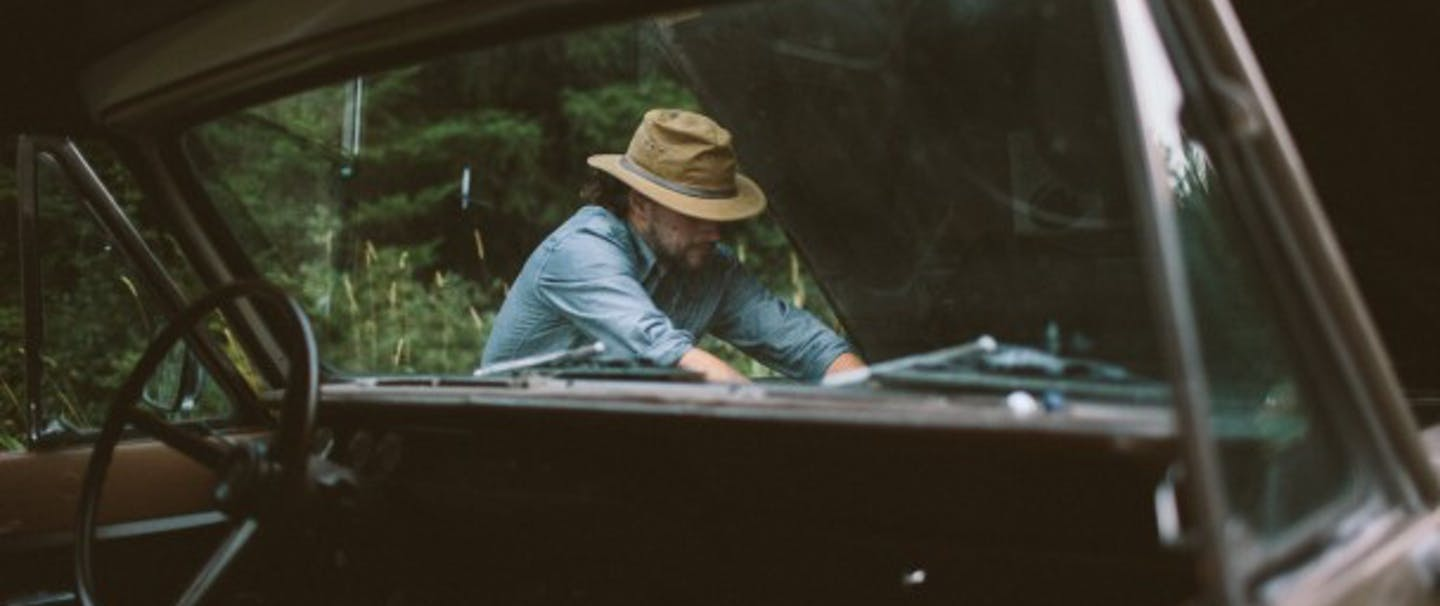 man in denim shirt and flat-brimmed hat works on hood of classic car