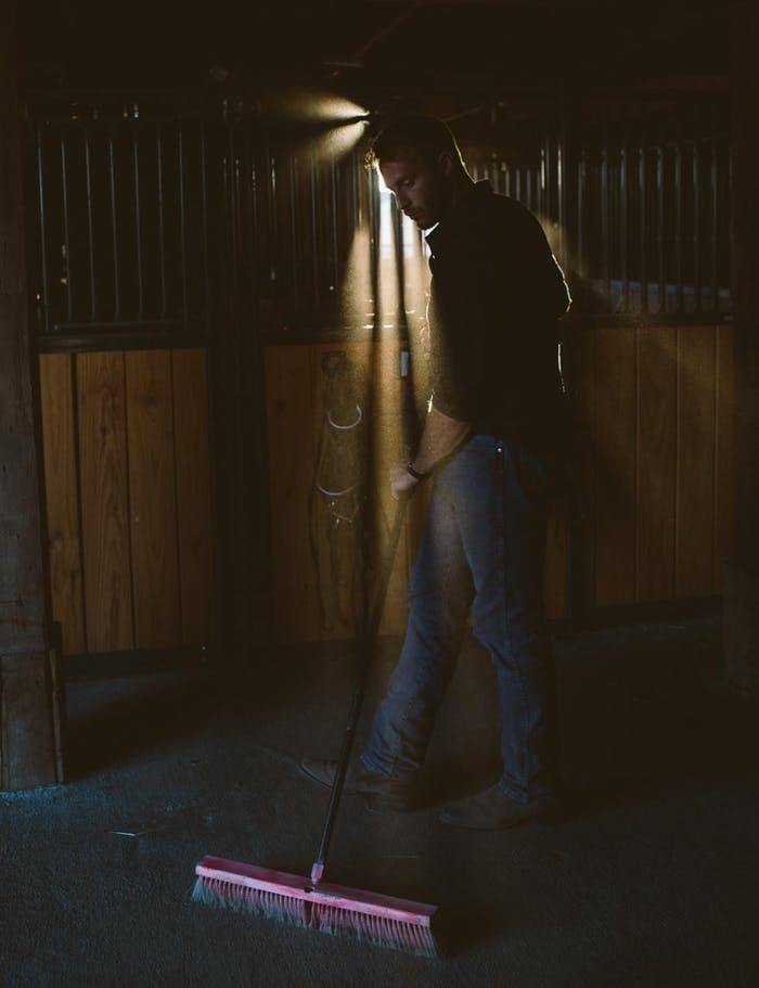 sunlight shines through horse stable bars and man sweeps stable floor