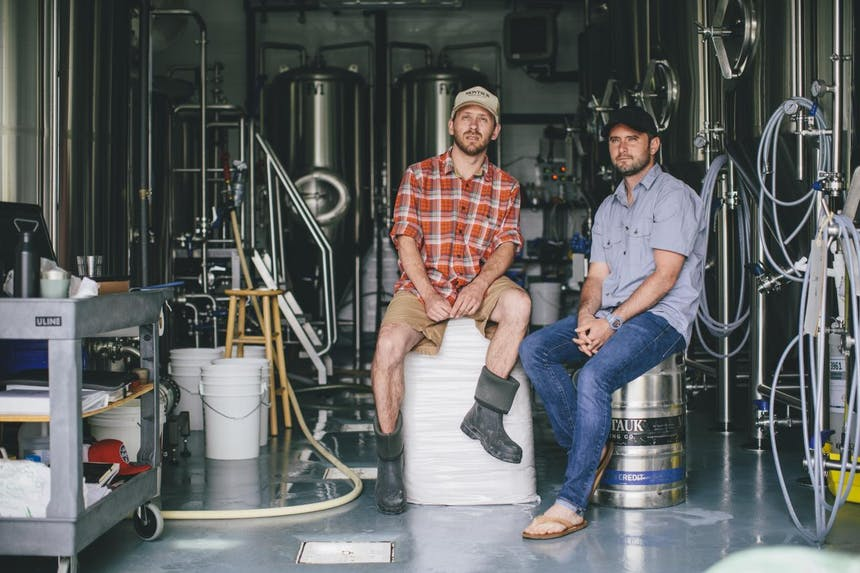 two guys sitting in a brewery