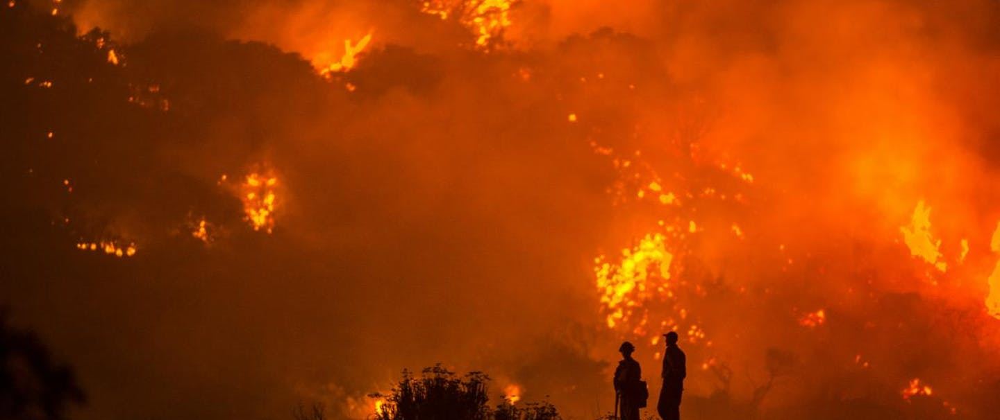 two firefighters silhouetted by raging fire in background