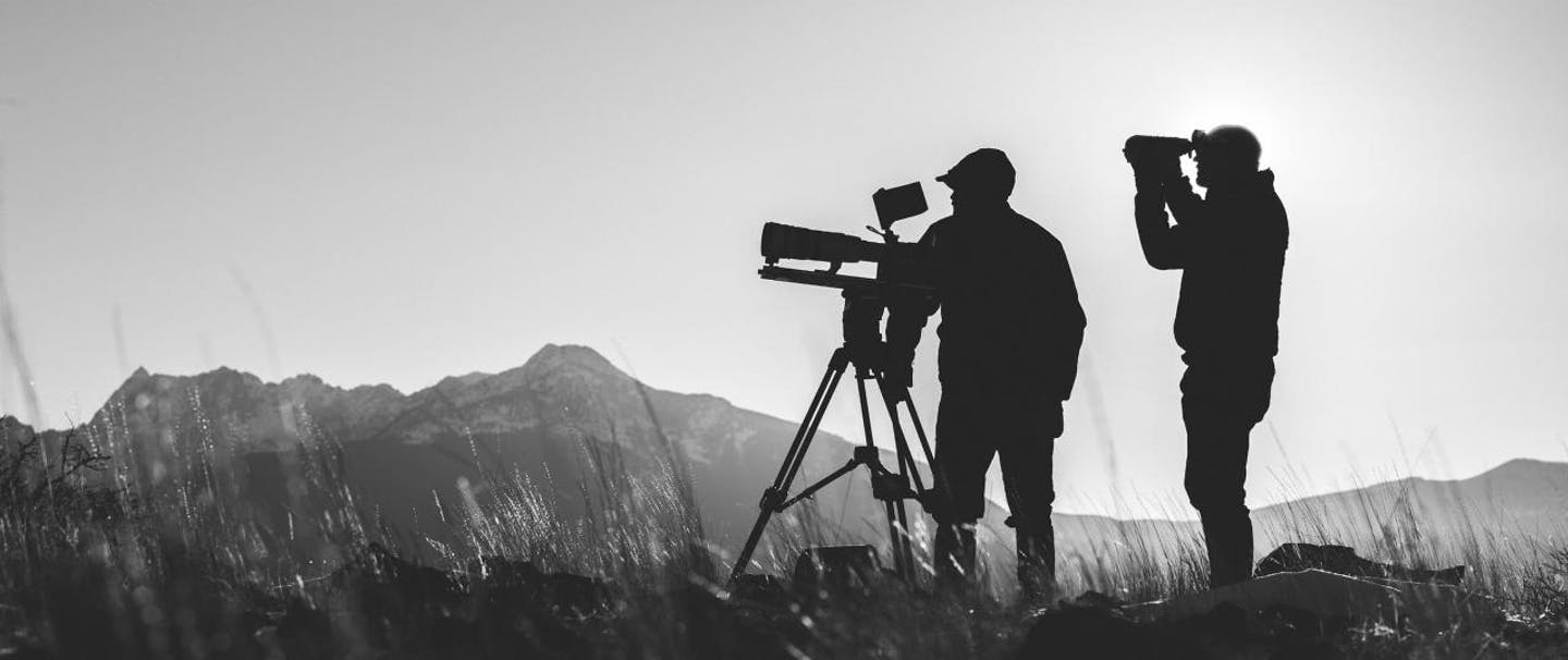 silhouette of two men looking through telescopic lens and binoculars in grassy field