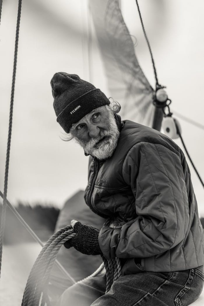 chad kirkland on sailboat holding a coiled rope in port townsend