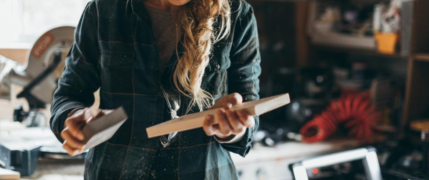 woman hand sands small piece of wood in workshop