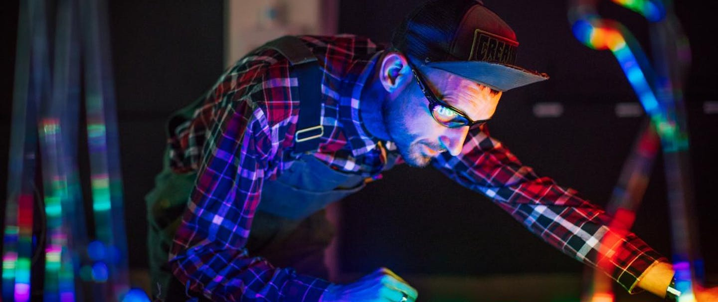 man with upturned bill of cap works over neon lights