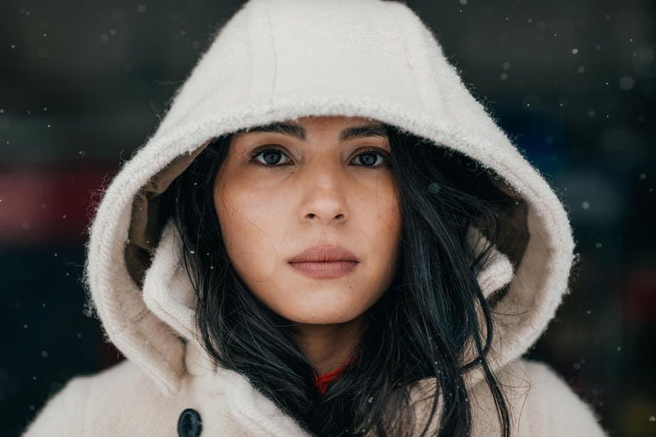 Keya portrait in white wool hooded jacket falling snow