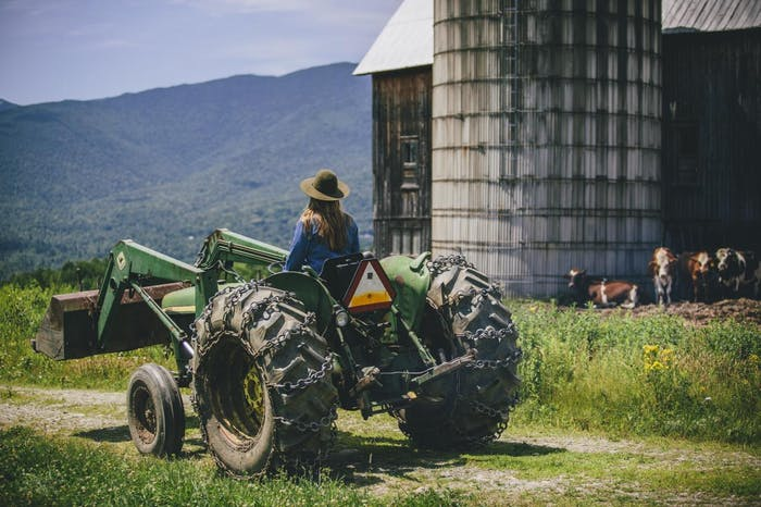 Marisa on a tractor with silo and mountains in background
