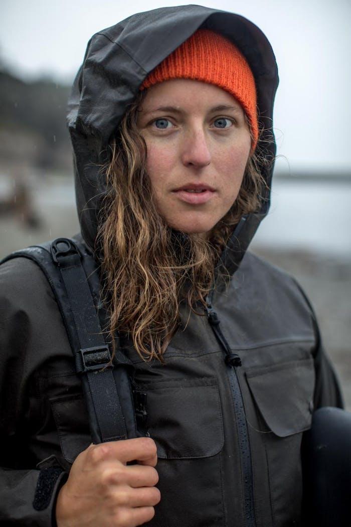 claire portrait in black raincoat with orange hat