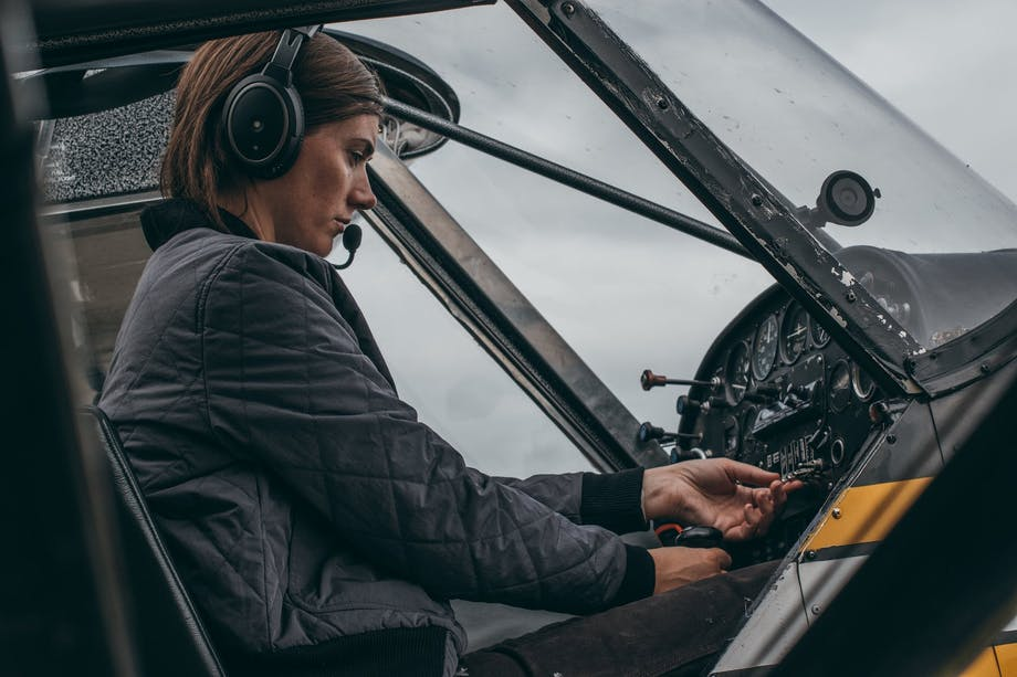 woman in black filson jacket sits in pilot seat of small aircraft touching switches