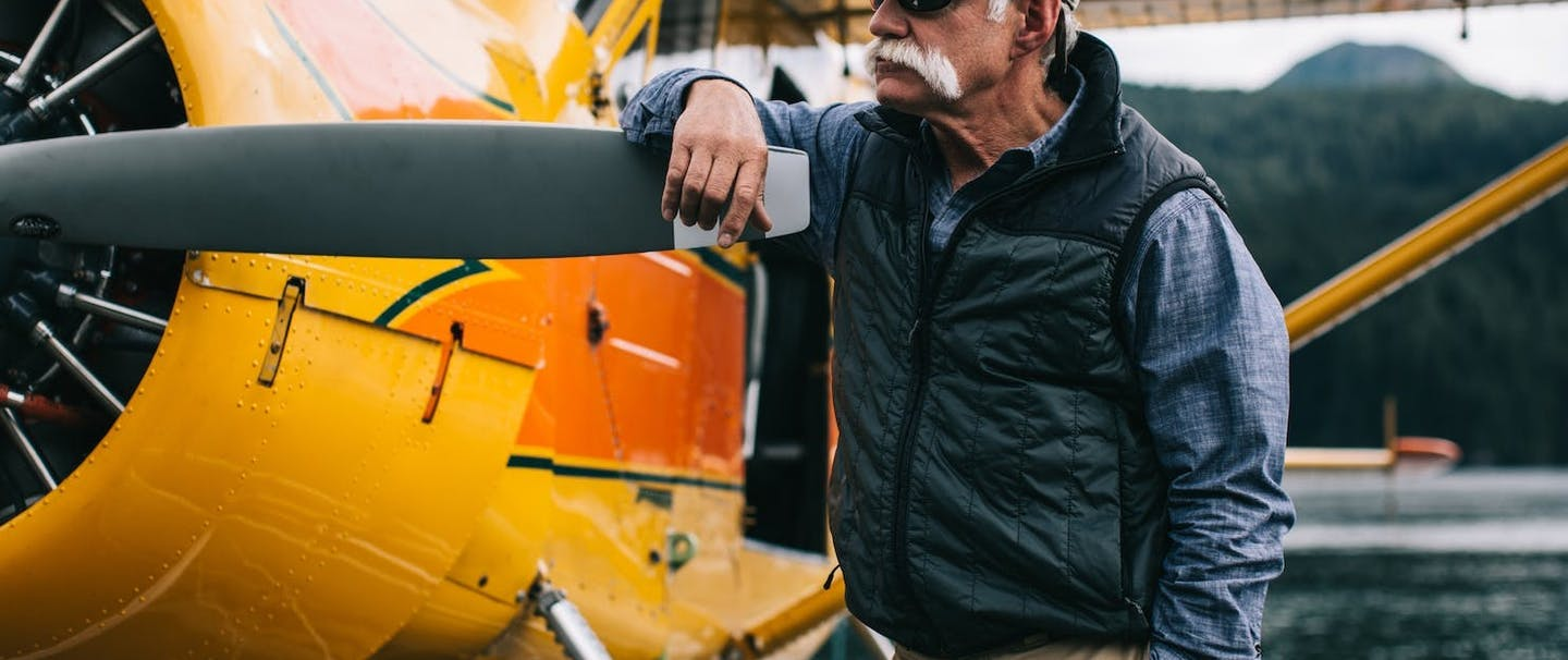 man with white mustachio stands with arm on propeller blade of orange sea plane