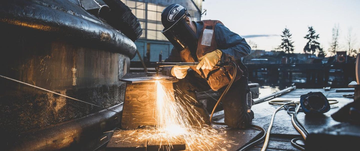 man in welding mask and vest cuts metal with plasma torch in boat yard