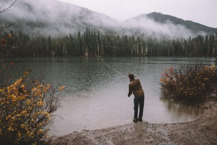 fly fisher casts into lake with pine trees and low lying clouds