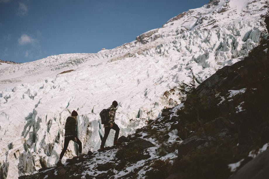two people hiking up the side of a glacier