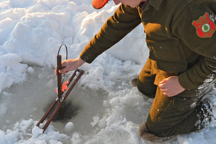 Ice Fishing - Man in olive wool coat and pants sets up ice fishing hole