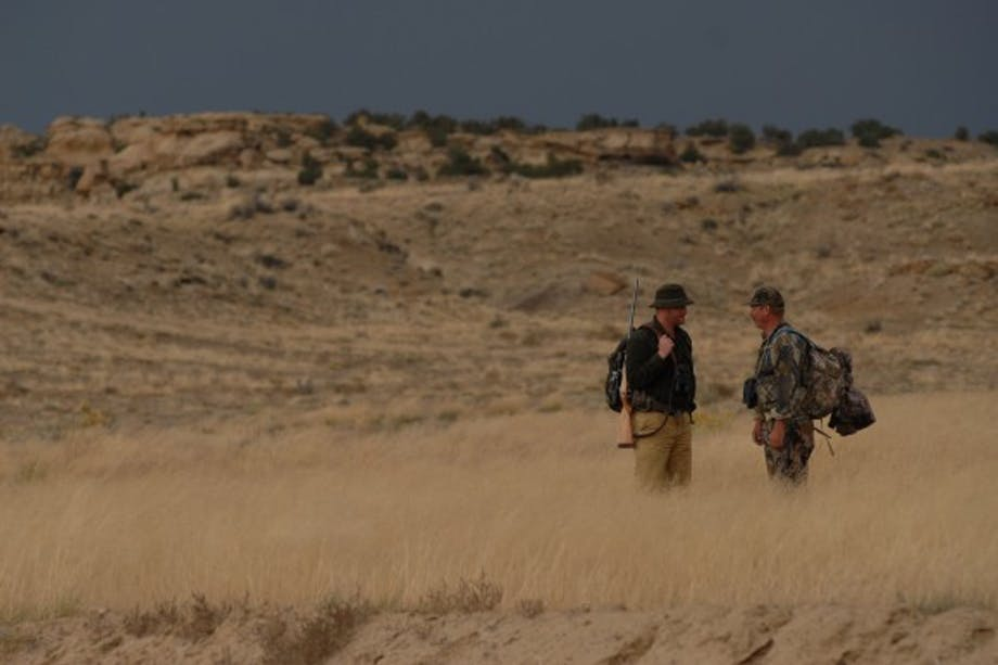 two hunters stand in yellow grass talking