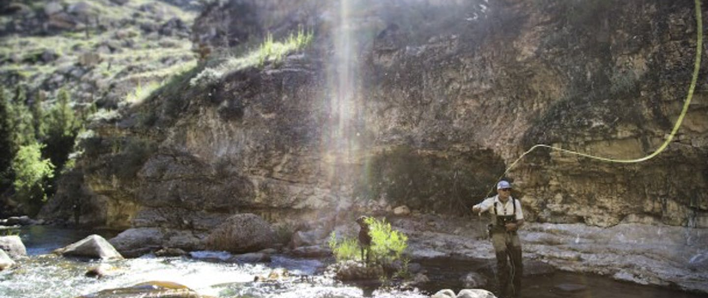 fly fisherman casting in rocky river