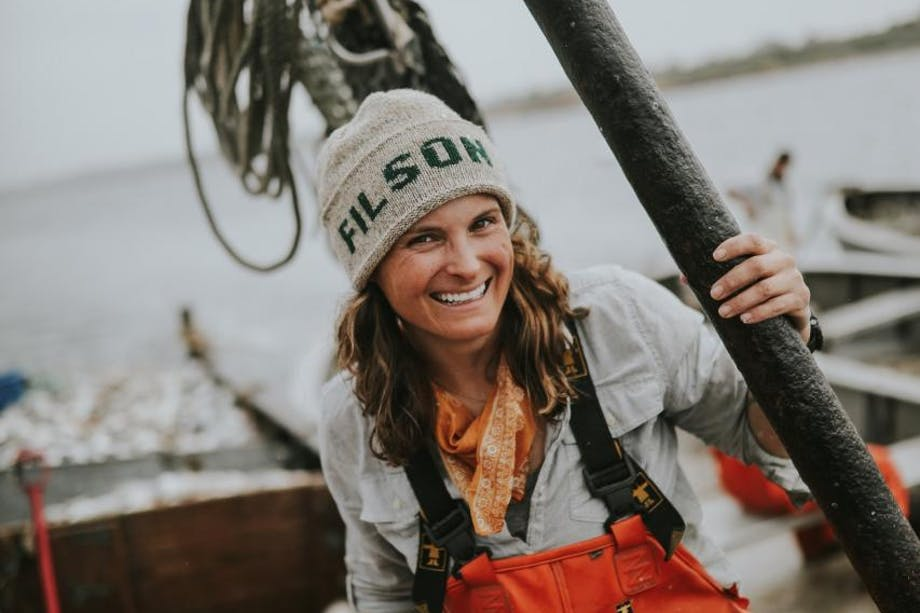 portrait of corey on fishing boat in filson hat and orange overalls