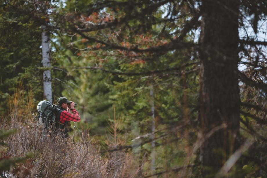 man in woods looks through binoculars wearing backpack and red flannel