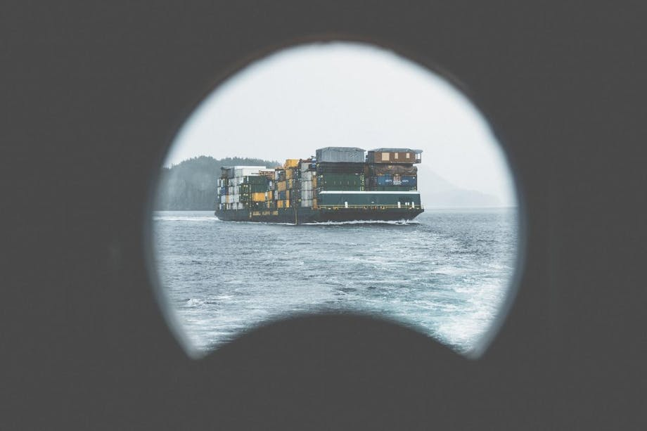 barge with trucking containers seen through porthole of another ship