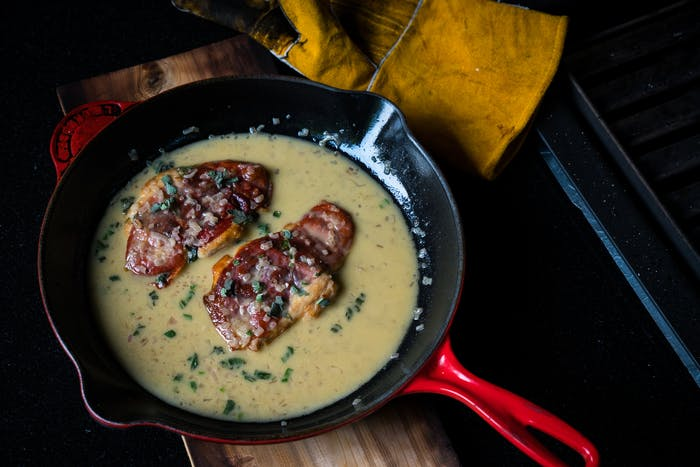 two pieces of meat in broth in cast iron skillet