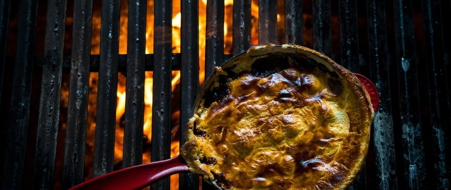 finished dish in cast iron skillet on glowing grill grates