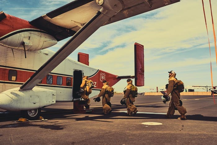 Smokejumper s enter red and white plane in full gear