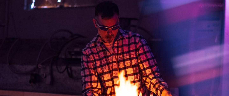 man bending glass tubes in plaid shirt