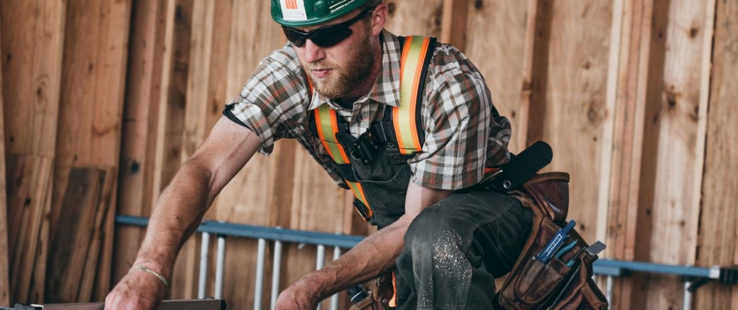 carpentry worker rips board in shortsleeve plaid shirt and hardhat