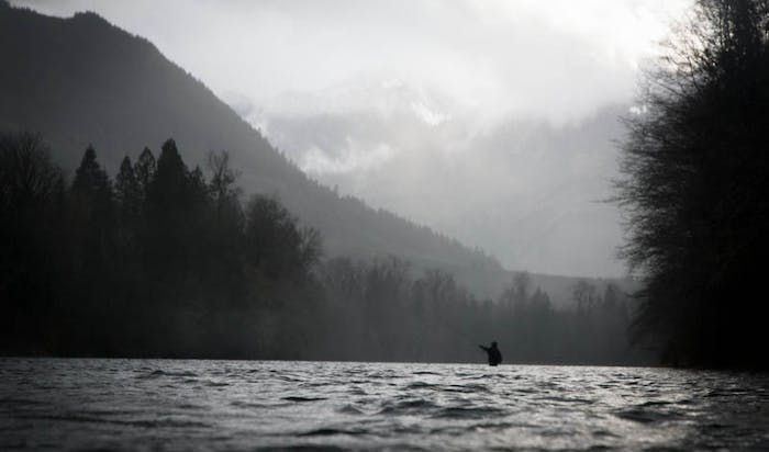 fly fisherman in river with alpine lined mountain ridge backdrop
