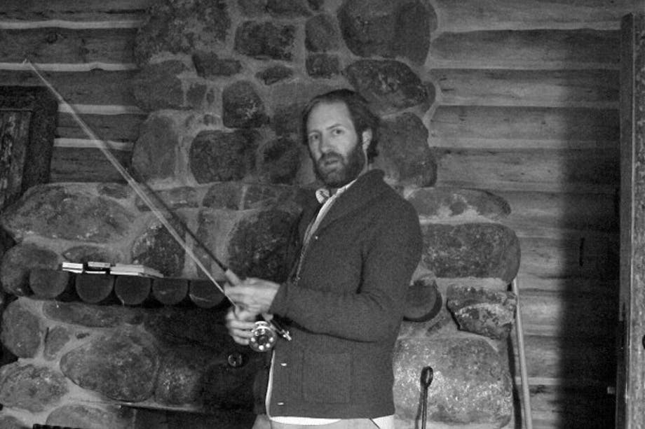 David Coggins in grey coat standing in front of stone fireplace holding fly fishing rod